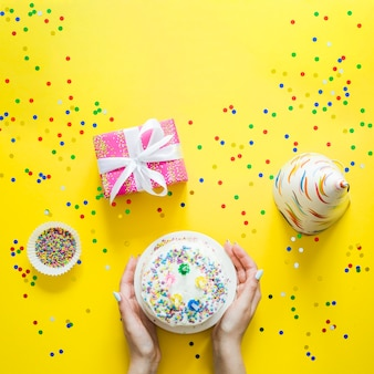 Hands with cake and confetti
