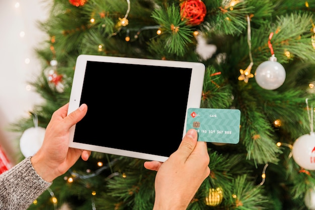 Hands with card and tablet at fir tree