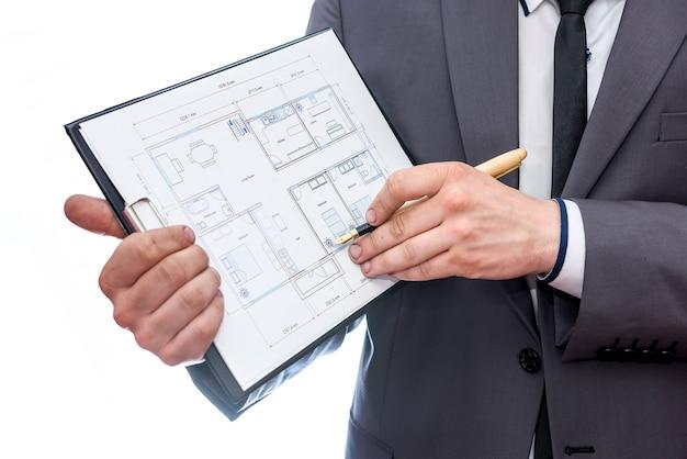 クリップボードと家の計画を持つ手がクローズアップ