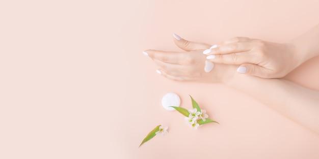 リンゴのクローズアップの白い花とクリーム色の手。スキンケア製品、美容、ハンドケア、スパ。