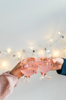 Hands with cup of drinks near fairy lights