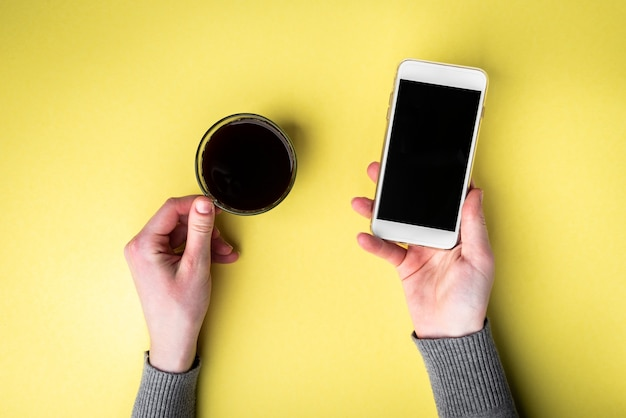黄色の背景にコーヒーと携帯電話のカップを持つ手。