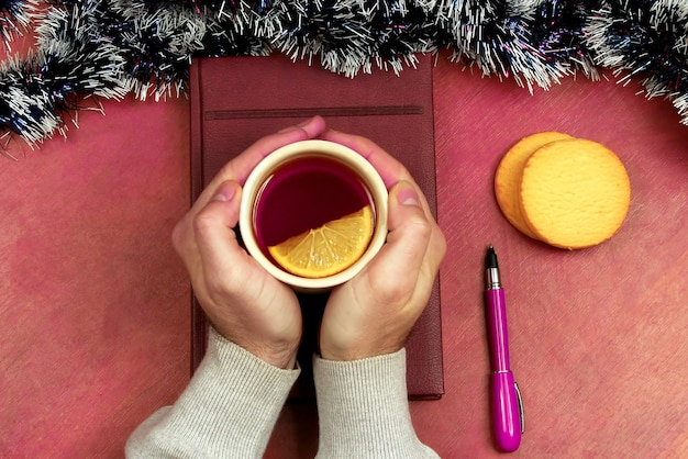 The hands with a cup of tea on the office table before the new year