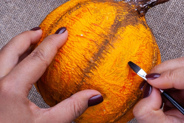 暗いマニキュアペイントの手とガッシュオレンジ色のブラシでハロウィーンの張り子からカボチャをクラフト