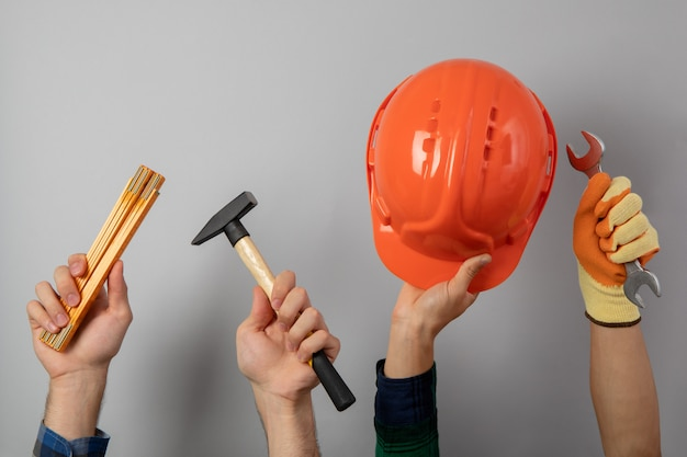 Hands with different construction tools