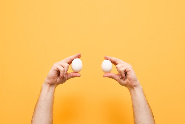 Руки с яйцами изолированы на желтом