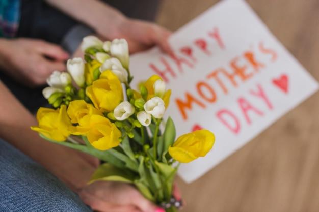 Руки с цветами и знаком матери