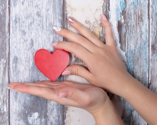 赤いハートを保持しているジェルの爪と手