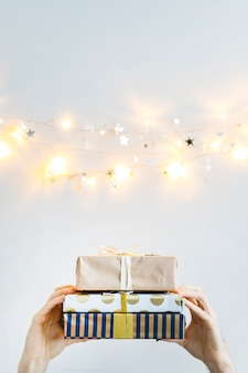 Hands with gift boxes near fairy lights and ornament stars