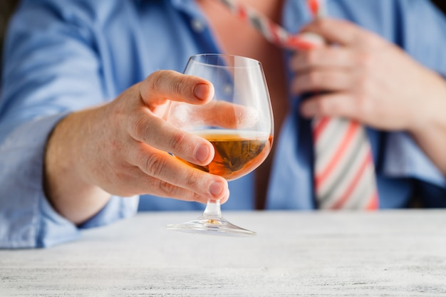 Hands with glass of cognac. focus on hand with glass