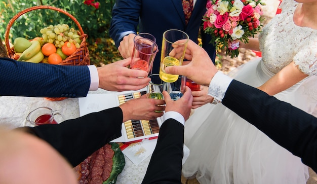 Hands with glasses of cocktails in the hands of a group of friends