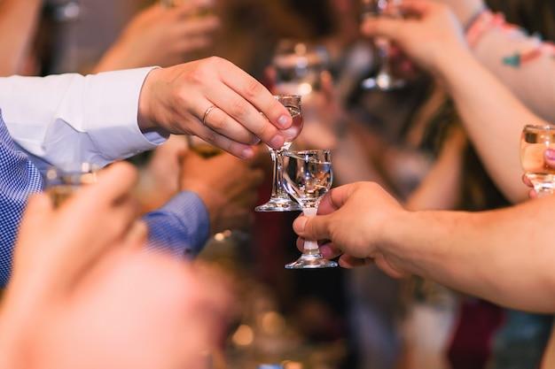 Руки с бокалами водки, празднование традиционного русского праздника Premium Фотографии