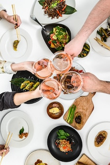 Hands with glasses of rose wine for a family, friendly dinner in the asian style. dumplings, spring rolls, wok noodles, steaks, salads