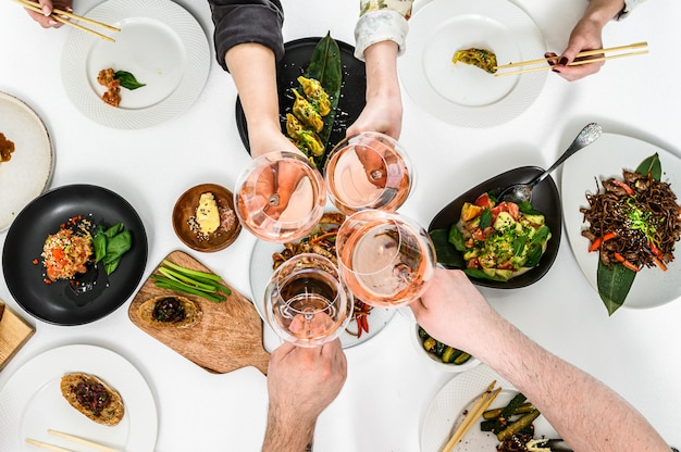 Hands with glasses of rose wine for a family, friendly dinner in the asian style.