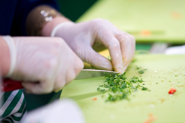 Hands with gloves cutting parsley
