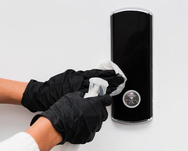 Руки в перчатках, дезинфицирующие дверной звонок