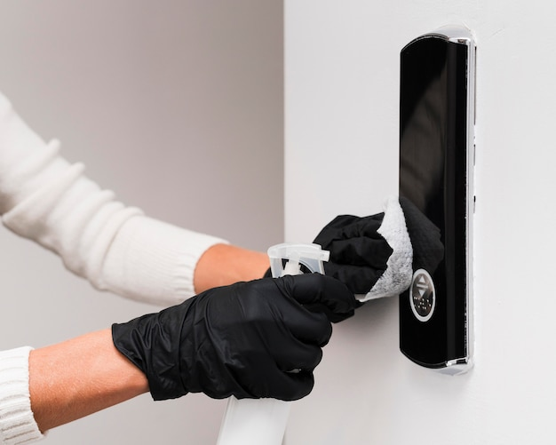 Hands with gloves disinfecting door bell