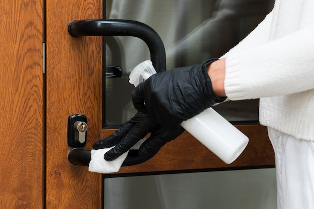 Руки в перчатках, дезинфицирующих дверную ручку