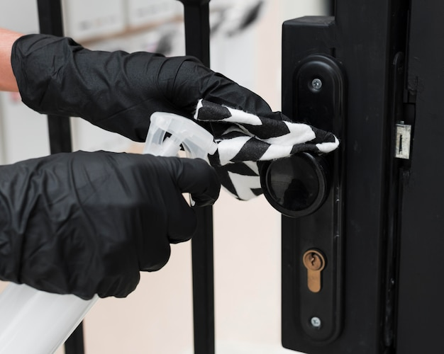 Hands with gloves disinfecting gate handle