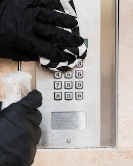 Руки в перчатках, дезинфицирующих переговорное устройство