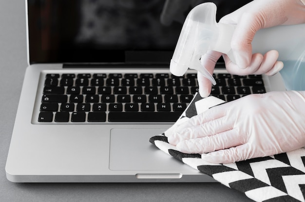 Hands with gloves disinfecting laptop with solution