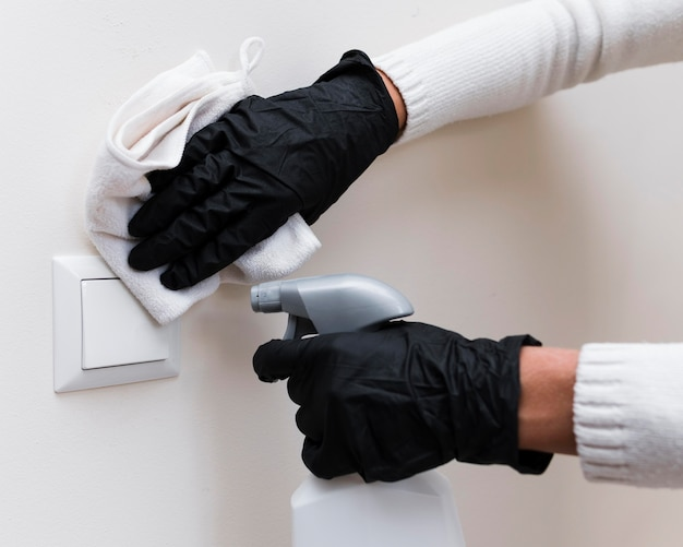 Hands with gloves disinfecting light switch