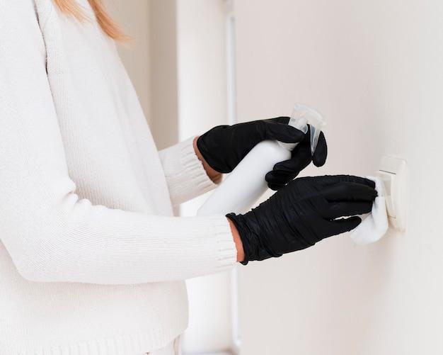 Руки в перчатках дезинфицируют выключатель света