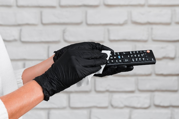Hands with gloves disinfecting remote control