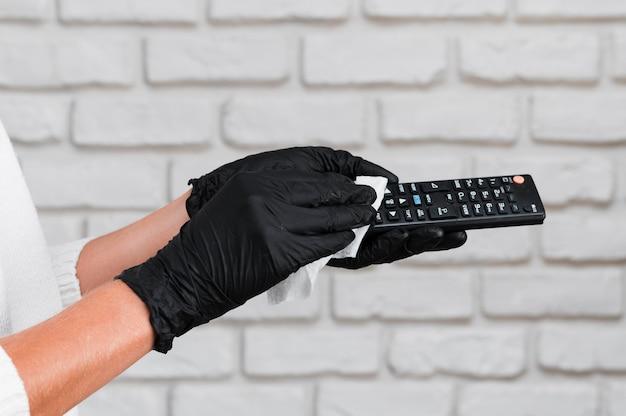 Руки в перчатках, дезинфицирующих пульт дистанционного управления