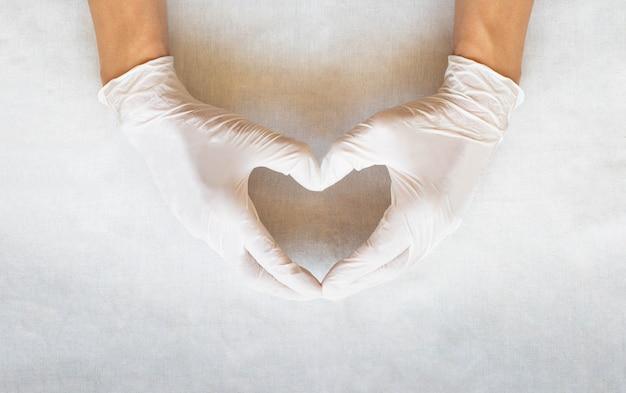 手袋をした手はハートの形を身振りで示します。心臓の健康、愛、メンタルヘルスケア、医療手術。