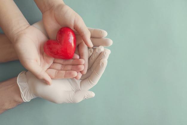 Руки в перчатках, взявшись за руки ребенка и красное сердце, концепция медицинского страхования и пожертвования