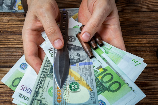 Hands with handcuffs, knife and ammunition with money banknotes.