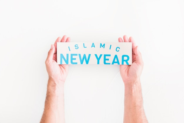 Hands with islamic new year paper