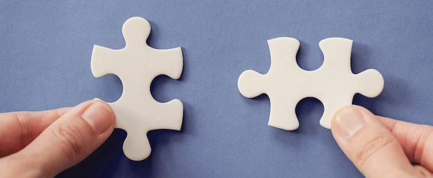 Hands with jigsaw puzzle pieces, business strategy planning, alzheimer's disease, autism and mental health concept