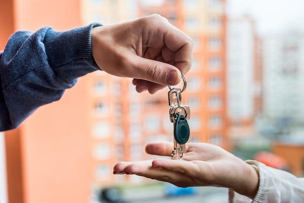 新しいアパートとドルの束からの鍵を持つ手