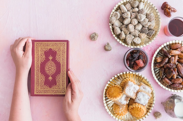 Hands with koran at sweets