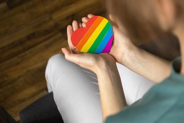 Lgbt 무지개 기호가 있는 손. 다채로운 심장 클로즈업입니다. lgbtq, 레즈비언 및 게이 권리, 자부심의 달 및 관용 배경 사진