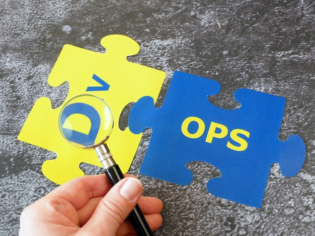 단어 dev 및 ops 퍼즐이있는 돋보기 유리로 손