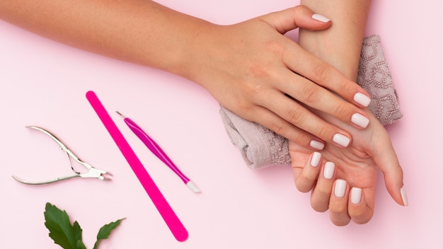 Hands with manicure done and nail care tools