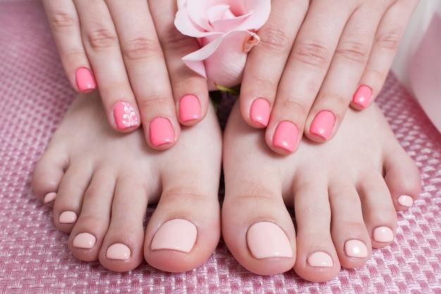 Руки с маникюром, ноги с педикюром. женские руки и ноги на розовом фоне вид сверху. результат процедуры спа салона