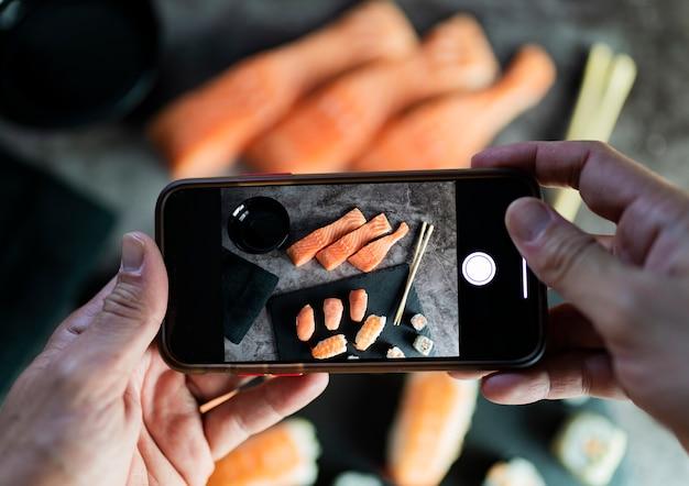 Руки с мобильным телефоном фотографируют суши азиатской кухни
