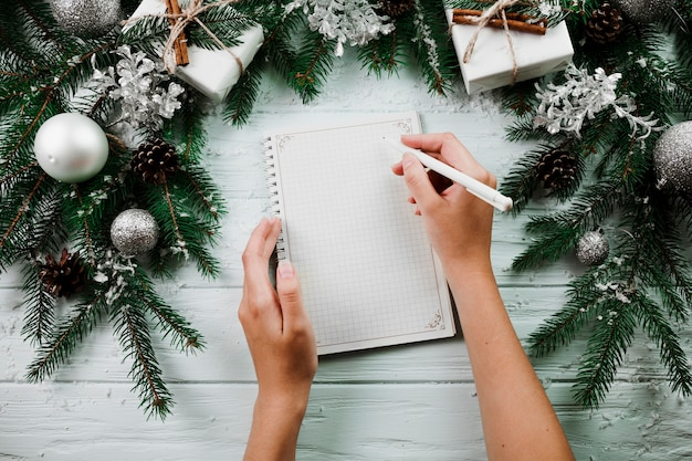 Hands with notebook near christmas branches