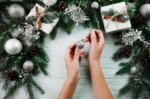 Hands with ornament ball near fir twigs