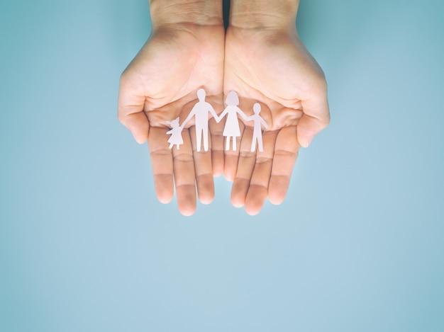 Руки с семьей вырезать из бумаги на синей поверхности