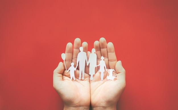 Руки с семьей вырезать из бумаги на красной поверхности