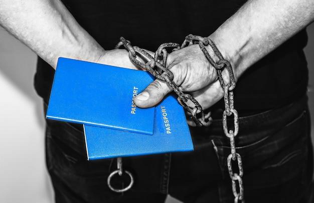 古いさびたチェーンのパスポートを持つ手。不法移民で逮捕された。法律を破った。密輸の概念。