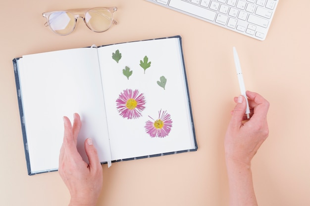Hands with pen near notebook with dry flowers, keyboard and eyeglasses