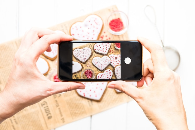 Hands with the phone close-up pictures homemade cookies for valentine's day sprinkled with hearts on a light background