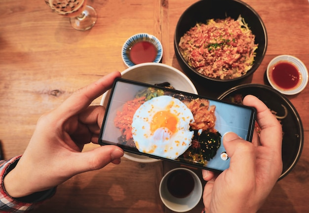 Hands with the phone takes picture of korean food with fried egg