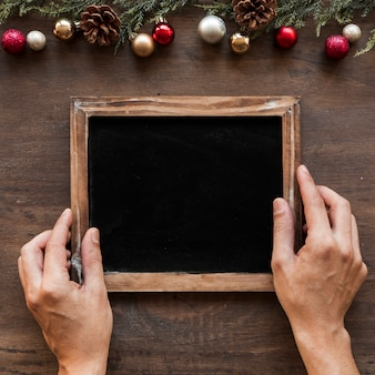 Hands with photo frame near christmas decorations